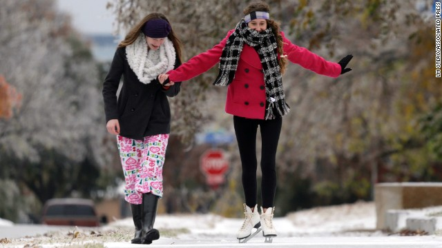 Jane Giles, 15, right, gets some help from her sister Sarah Giles, 17, as she skates on an icy sidewalk in Richardson, Texas, on December 6.