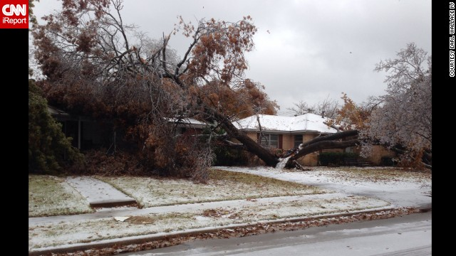 A tree, split in two, lays on two homes on December 6 in Dallas in this photograph taken by CNN iReporter <a href='http://ireport.cnn.com/docs/DOC-1066368'>Earl Wallace IV</a>.