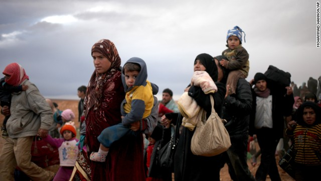 Newly arrived Syrian refugees carry their belongings and children after crossing into Ruweished, Jordan, on December 5.