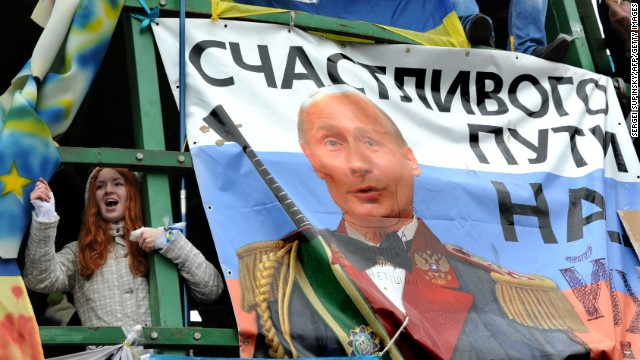 "A young protester shouts slogans near a placard depicting Russian President Vladimir Putin and signed ""Fare you well!"" during the December 8 rally."
