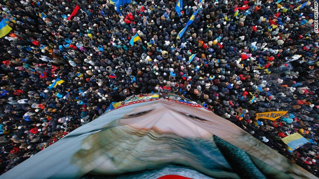 Pro-EU activists gather around a huge poster of Yulia Tymoshenko, the jailed former Ukrainian Prime Minister, on December 8.