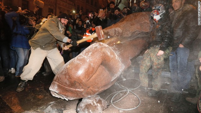 A protester in Kiev slams a toppled monument of Vladimir Lenin on December 8.
