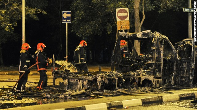 Firemen douse a charred ambulance in the early hours of December 9, 2013, after a fatal traffic accident sparked a riot in Singapore's Little India district.