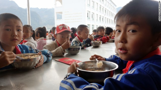 The children eat lunch at an outside cafeteria.