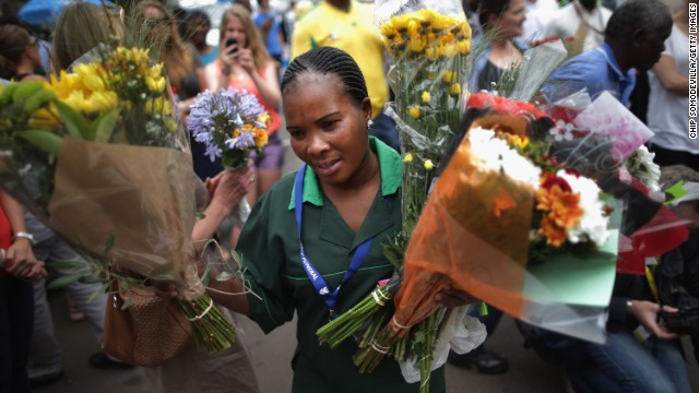 A groundskeeper collects flowers left by visitors at Mandela's home in Johannesburg on December 9.