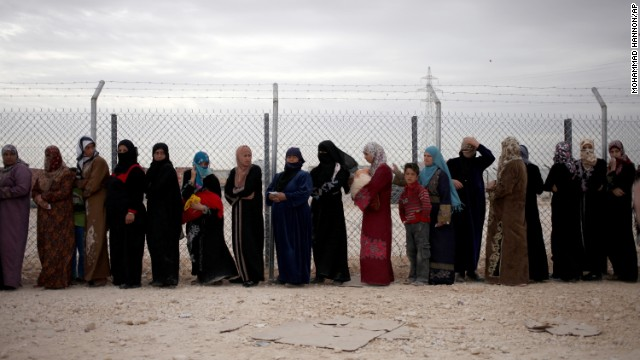 Syrian refugees wait in line to receive winter aid kits at Zaatari refugee camp in Mafraq, Jordan, on Tuesday, December 3.