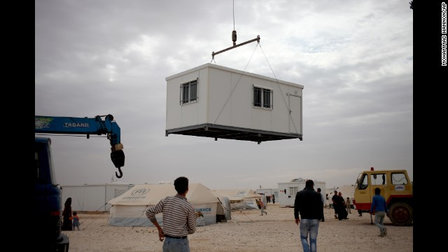 Refugees watch a new trailer being placed in the Zaatari camp as part of the winter preparations in Mafraq, Jordan, on December 3.