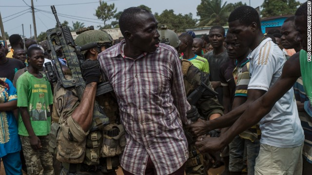 People gather around an alleged ex-Seleka rebel as he is arrested by French soldiers in Bangui on December 9.