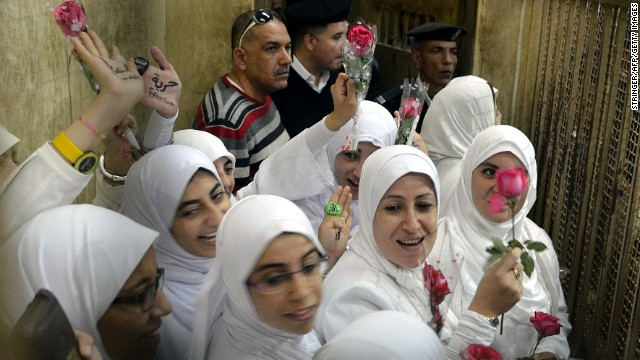 Egyptian women members of the Muslim Brotherhood hold roses as they stand in the defendants' cage dressed in prison issue white