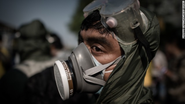 A demonstrator wearing a gas mask looks on outside a government building in Bangkok on December 9.