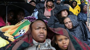 People shelter under blankets and umbrellas during the memorial service for former South African President Nelson Mandela at FNB Stadium in Johannesburg on Tuesday December 10.