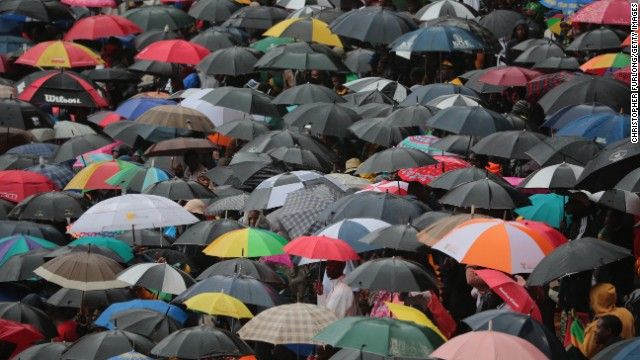 People take shelter under umbrellas at FNB Stadium.