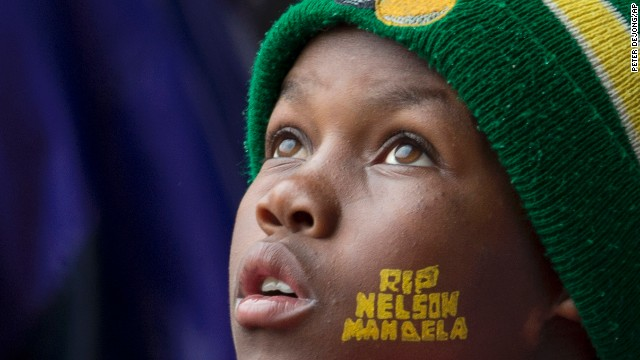"A boy looks up during the memorial service at FNB Stadium. He has ""RIP Nelson Mandela"" painted on his face."