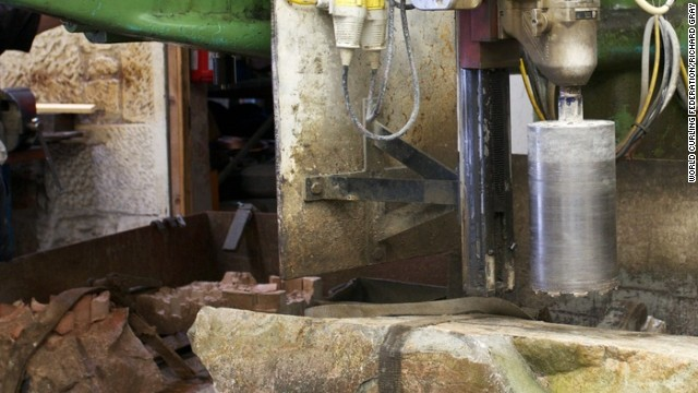 A machine cores a hole into the base of the curling stone, in this case the common green stone, and a mold of separate granite is added to make an even higher quality product.