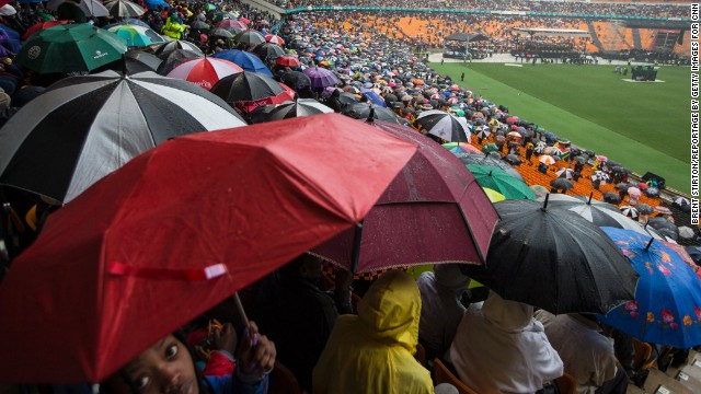 People in the stadium take shelter from the rain.