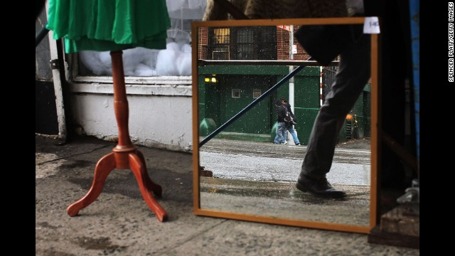 A mirror reflects light snow on a sidewalk in New York on December 10.