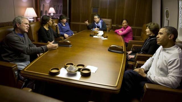 Former President George W. Bush, left, first lady Michelle Obama, senior adviser Valerie Jarrett, assistant to the president Tina Tchen, National Security Adviser Susan Rice, former first lady Laura Bush and President Barack Obama talk as they wait for dinner aboard Air Force One. The presidents were heading to South Africa for the memorial service of Nelson Mandela. White House photographer Pete Souza provided a behind-the-scenes look at the flight and their time in South Africa.