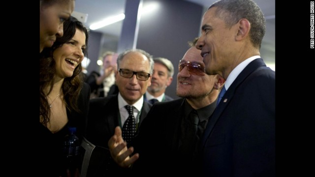 The Obamas talk with musician Bono at the memorial service.