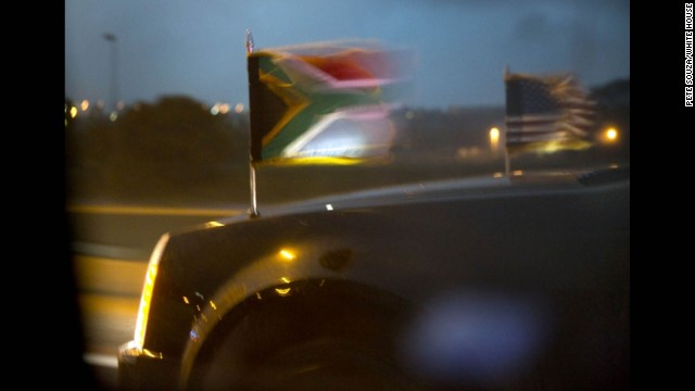 The South African flag flaps in the wind alongside the U.S. flag as the presidential motorcade speeds to the airport.