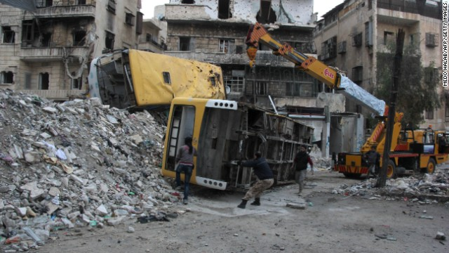 Rebel fighters in Aleppo fortify a barricade with destroyed public buses on Wednesday, December 4.