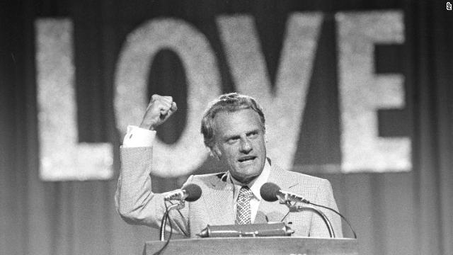 "Graham speaks to a crowd of 18,000 on the closing night of the Southern Baptist Convention in Dallas on June 13, 1974. The theme of the convention was ""Share His Love Now."""