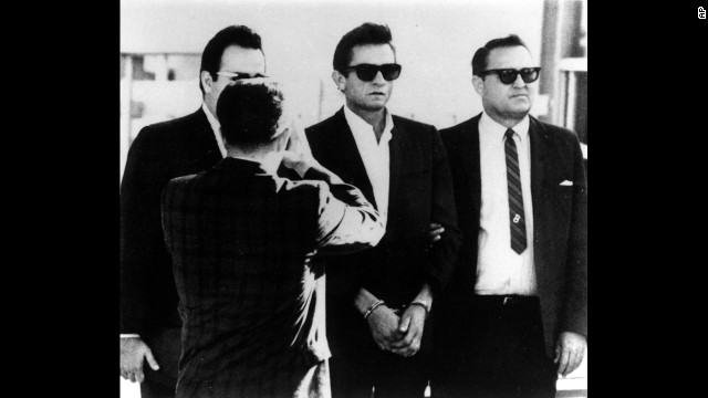 Cash, center, is flanked by a bondsman and a U.S. marshal as he is transferred to the federal courthouse in El Paso, Texas, on October 5, 1965. Cash was arrested and charged with importing and concealing over 1,000 pep pills and tranquilizers.