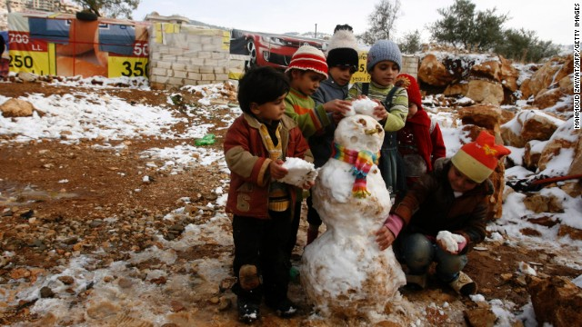 Young Syrian refugees build a snowman following a storm in a makeshift refugee camp in the Lebanese village of Baaloul in the Bekaa Valley on Thursday, December 12.
