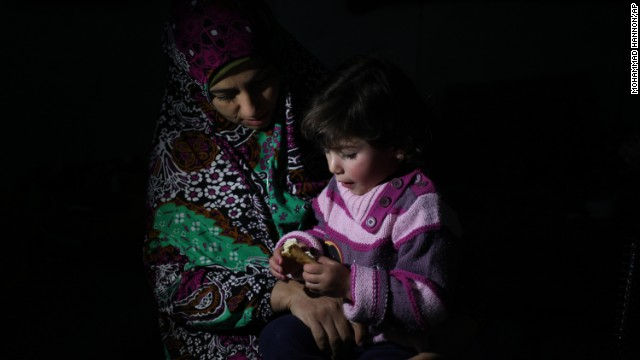 Syrian refugee widow Ikhlas Halawani feeds her daughter breakfast during a snowstorm in Amman, Jordan, on December 12.