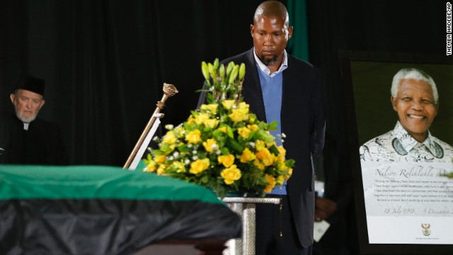Mandela's grandson Mandla Mandela walks by his grandfather's casket during a farewell ceremony at Waterkloof air base.