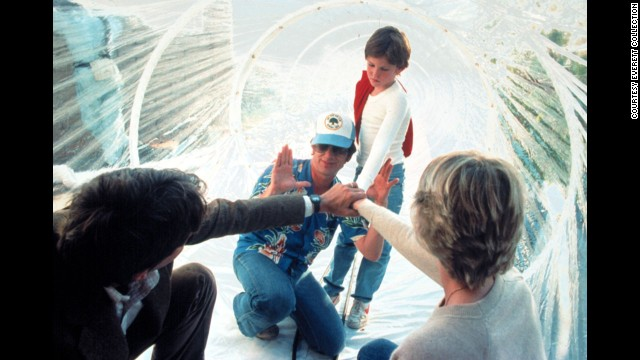 "Spielberg, wearing a hat, works with actors Peter Coyote, Henry Thomas and Dee Wallace during the filming of ""E.T.; The Extra-Terrestrial"" in 1982. As of 2013, the movie had made more than $792 million worldwide."