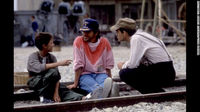 "Actor Christian Bale, left, Spielberg and John Malkovich talk on the set of ""Empire of the Sun"" in 1987. The film is taken from J.G. Ballard's novel based on Ballard's experiences as a boy in a Japanese prison camp during World War II."