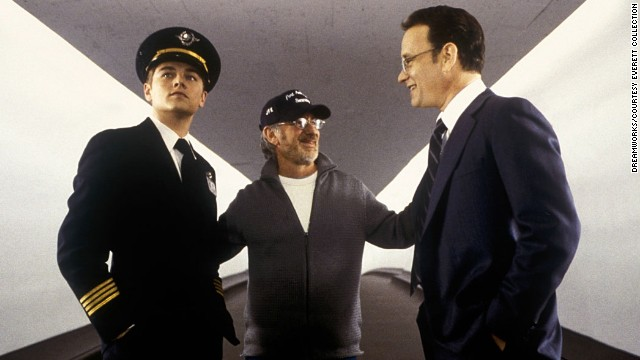 """Spielberg, center, works with actors Leonardo DiCaprio, left, and Hanks on the set of """"Catch Me if you Can"""" in 2002."""