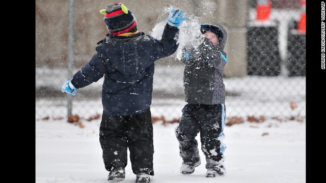 Landon Jackloski, left, and Patrick Craig engage in a snow fight on December 14 as snow falls during the tree-lighting ceremony at Forty Fort Park in Forty Fort, Pennsylvania.