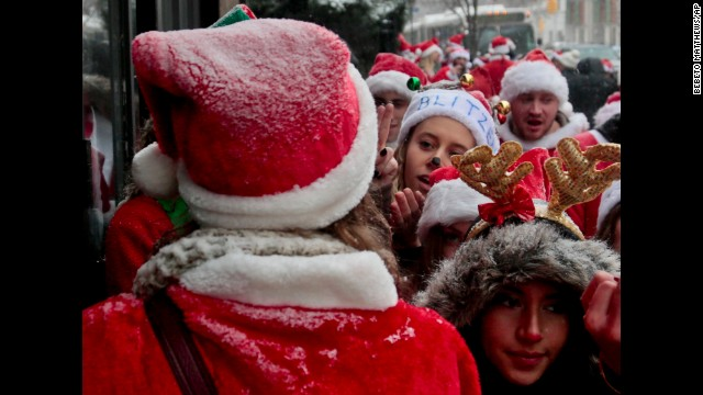 Snow-dusted Santas wait outside a capacity-filled bar on the Lower East Side.