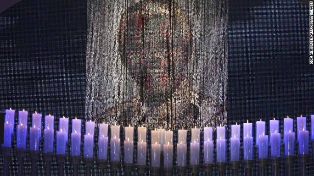 Candles are lit under a portrait of Mandela before the funeral ceremony.