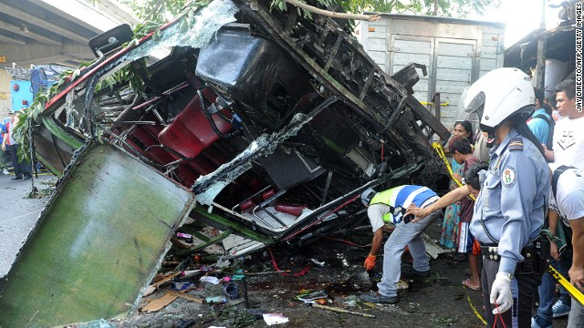 A highway patrol officer collects passengers' belongings from the bus that fell from an elevated highway in Manila.
