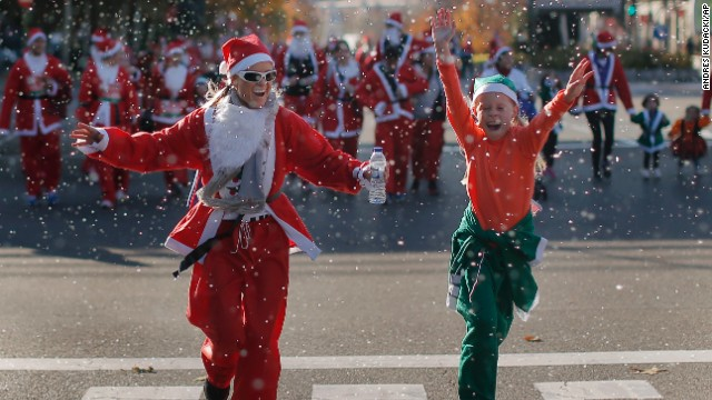 Revelers dressed as Santa Claus run under fake snow during a mini-marathon in Madrid on December 14.