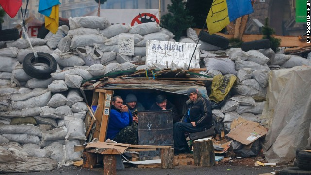 Activists warm themselves beside a bonfire as they guard barricades at Independence Square on Monday, December 16.