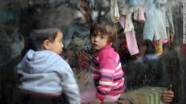 A child looks through a window while food and aid is distributed at a refugee center in Sofia, Bulgaria, on Tuesday, December 17. Bulgaria has taken in more than 10,000 Syrian refugees.