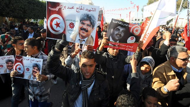 Tunisians carry portraits of assassinated opposition figure <a href='http://cnn.com/2013/07/25/world/africa/tunisia-politician-killed/index.html'>Mohamed Brahmi.</a>