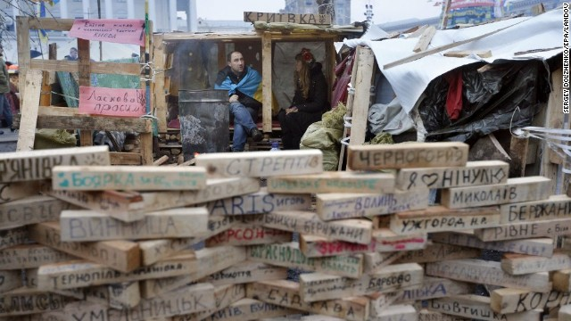 Protesters sit behind wood bricks in Independence Square on December 17. Written on the bricks are names of Ukrainian settlements whose inhabitants are taking part in the demonstrations.