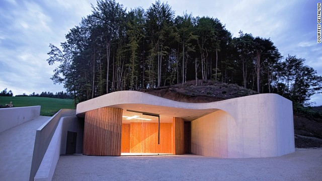 Located next to a graveyard outside of Ljubljana, this curvaceous chapel by Ofis Arhitekti mimics the slopes of the surrounding landscape.