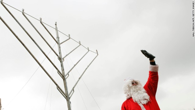 A man in a Santa Claus costume waves as he stands in front of a Chanukah menorah.