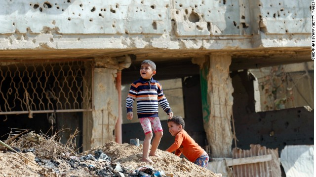 Palestinian children play in front of a house in Gaza in November that was damaged in an Israeli army operation in 2012.