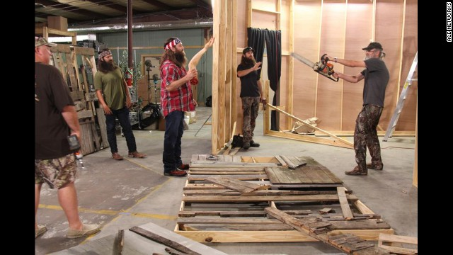 "The Duck Commander crew works on transforming their warehouse into a ""scarehouse"" during a recent Halloween episode. Holding the chainsaw is Si Robertson, who founded the company along with his brother Phil, not pictured."