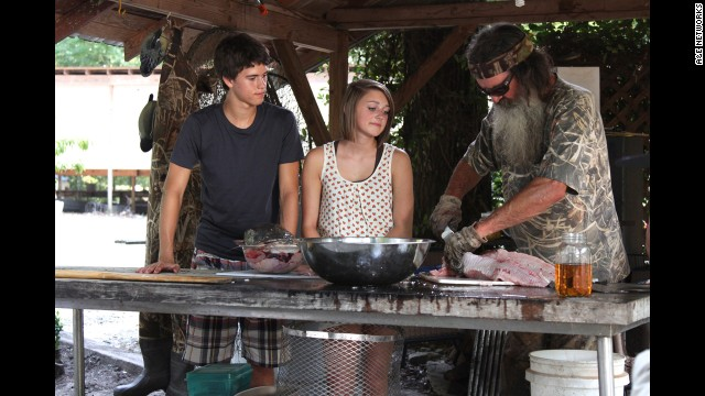 "Phil Robertson cuts meat during a recent ""Duck Dynasty"" episode. He was suspended by A&E in December after he made controversial remarks about gays and blacks in an interview with GQ magazine."