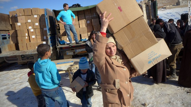 Syrian refugees unload relief supplies at the Shuhada Camp.
