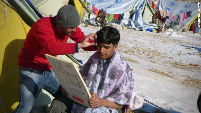 A Syrian refugee gets his hair cut at the Shuhada Camp.