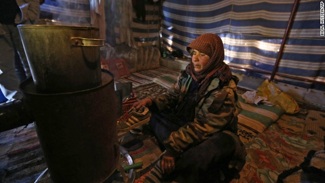 Syrian refugee Mariam al-Hamed burns an old shoe for warmth inside her tent at a refugee camp near Baalbek, Lebanon.
