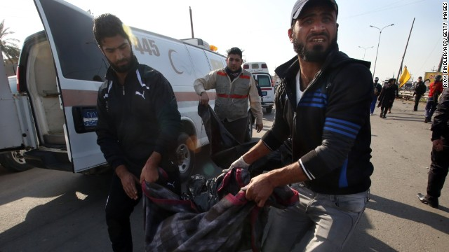 Iraqi men carry a victim of a suicide attack in the Dura area of south Baghdad on December 19.